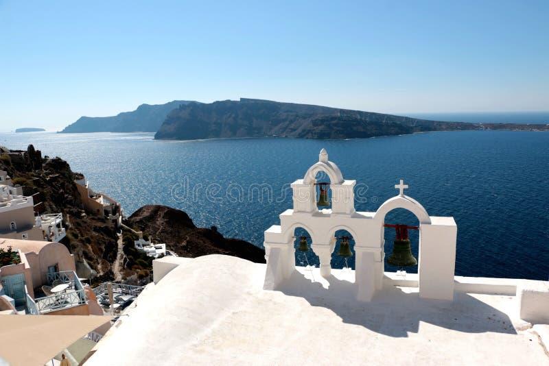 Vue de la surface de mer par la voûte blanche grecque traditionnelle d'église avec la croix et des cloches dans le village d'Oia  photos stock