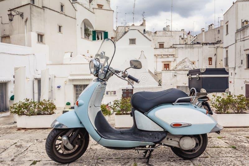 Vue de la vieille ville de Martina Franca V?lomoteur bleu classique sur le fond de l'b?timents anient photo libre de droits