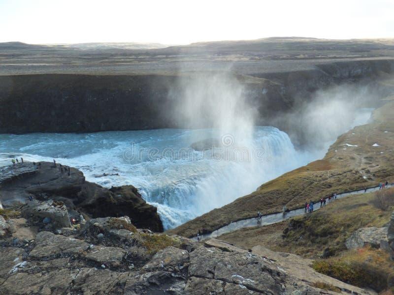 Vue de la voie d'accès à Gullfoss, cascade d'or, en Islande avec de petites figures des personnes et de la brume se levant de la  photos stock