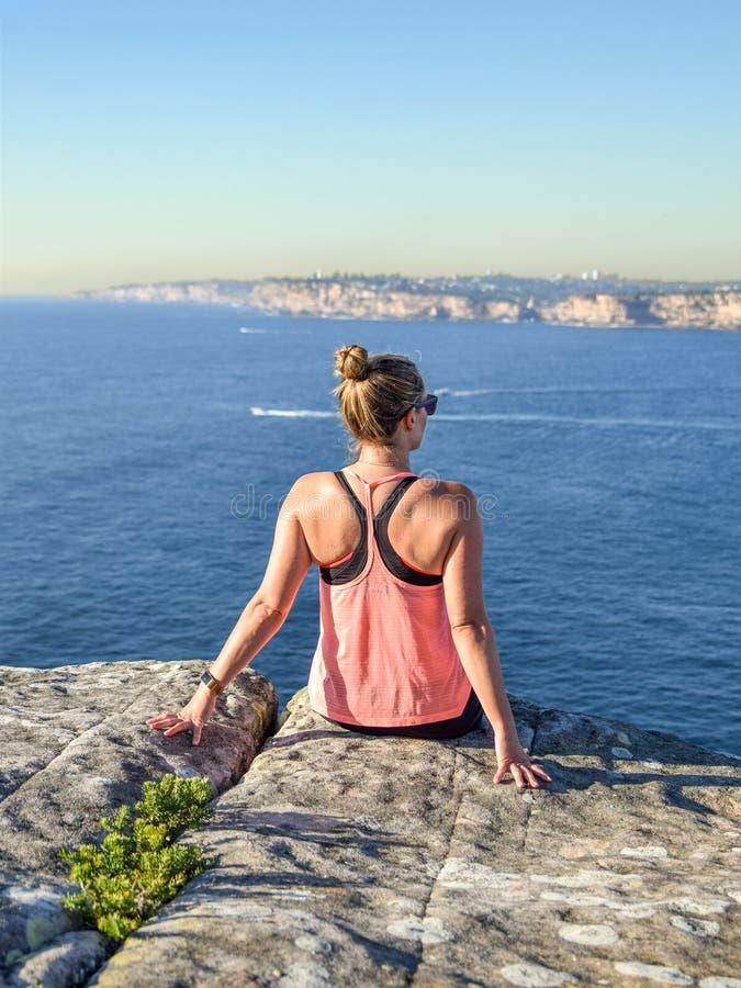 Vue de matin d'un jeune randonneur féminin s'asseyant sur une roche à la tête du nord, un promontoire dans viril photographie stock