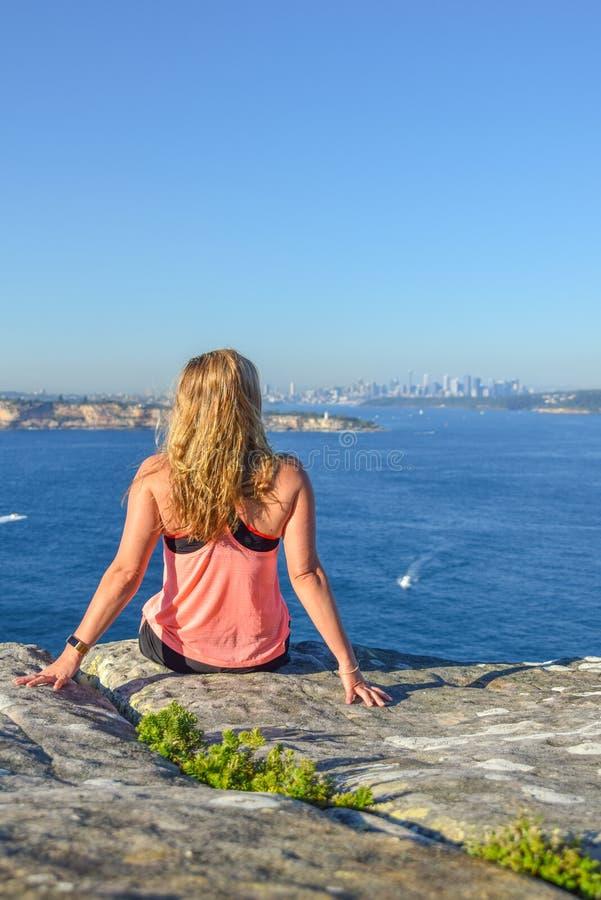 Vue de matin d'un jeune randonneur féminin s'asseyant sur une roche à la tête du nord, un promontoire dans viril photo stock