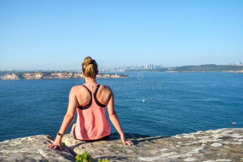 Vue de matin d'un jeune randonneur féminin s'asseyant sur une roche à la tête du nord, un promontoire dans viril image stock