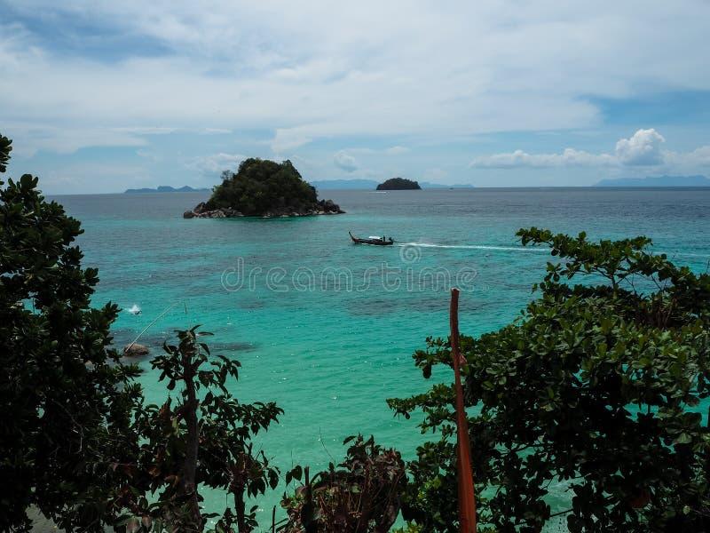 Vue de mer de turquoise avec le bateau de long-queue, la petite île et la SK bleue photographie stock libre de droits