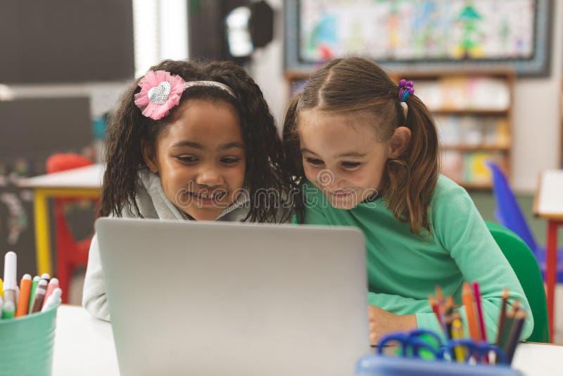 Vue de niveau extérieure de l'écolière deux souriant tandis qu'ils travaillant sur leur ordinateur photo libre de droits