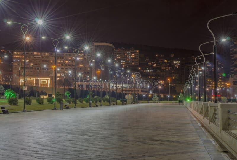 Vue de nuit de Bakou avec les tours de flamme et le boulevard national photos stock