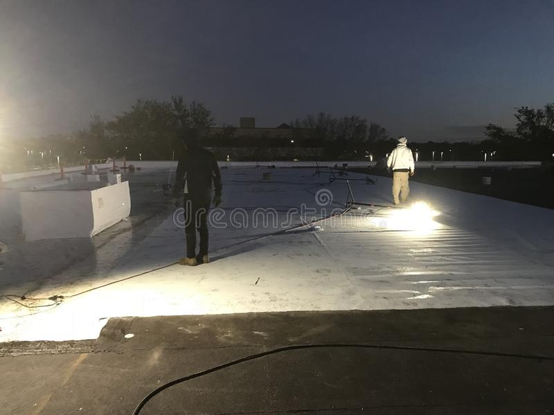 Vue de nuit des Roofers enlevant la feuille modifiée de chapeau du toit plat commercial pour la conversion en TPO avec des drapea photographie stock