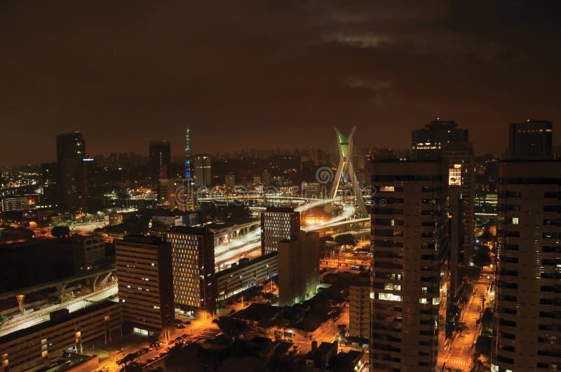 Vue de nuit de l'horizon de ville avec le pont et les bâtiments sous la lune nuageuse et pleine dans la ville de São Paulo photos libres de droits