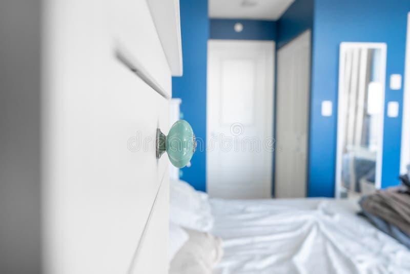 Vue de perspective d'une chambre à coucher montrant un bouton de raboteuse, des murs peints bleus, des accents blancs et un lit s photographie stock