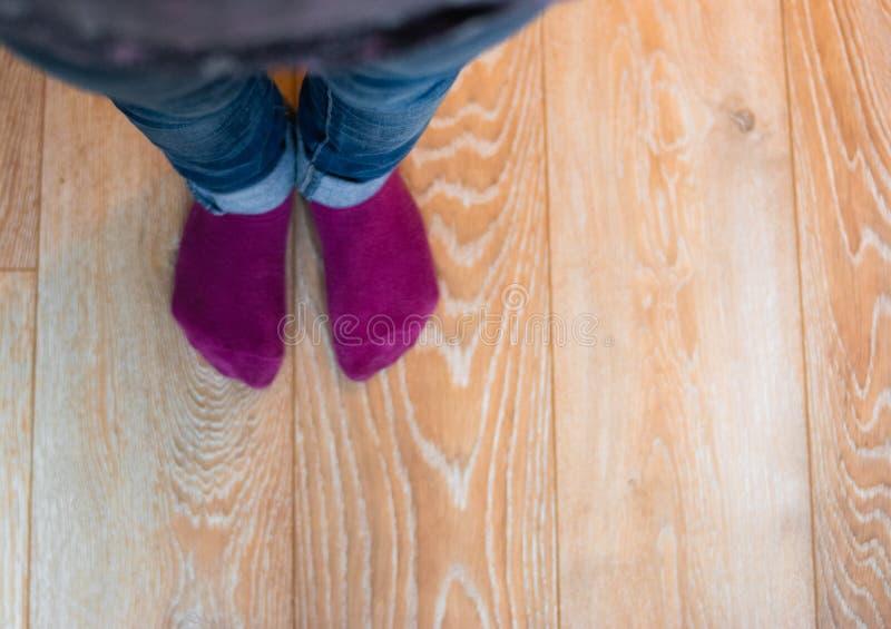 Vue de perspective des pieds du ` un s d'enfant avec les chaussettes et la blue-jean pourpres photo stock
