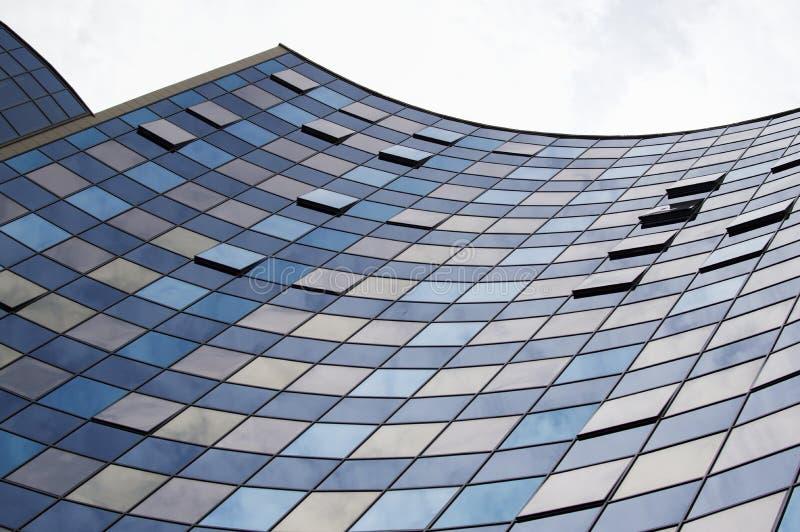 Vue de perspective de la façade en verre moderne de bâtiment avec des réflexions de nuages sur les fenêtres images stock