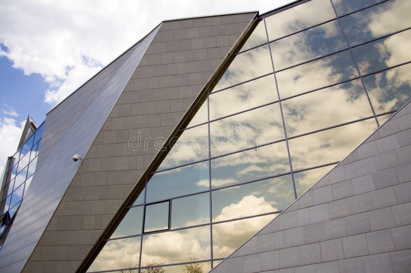 Vue de perspective de la façade moderne de bâtiment avec des réflexions de nuages sur les fenêtres photo libre de droits