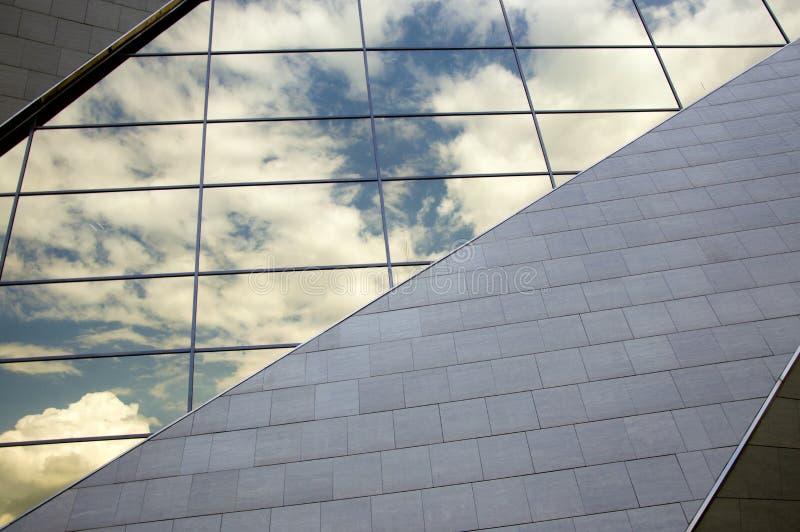 Vue de perspective de la façade moderne de bâtiment avec des réflexions de nuages sur les fenêtres photos libres de droits