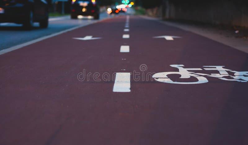 Vue de perspective de ruelle de vélo près de rue avec les voitures et les lumières brouillées photo stock