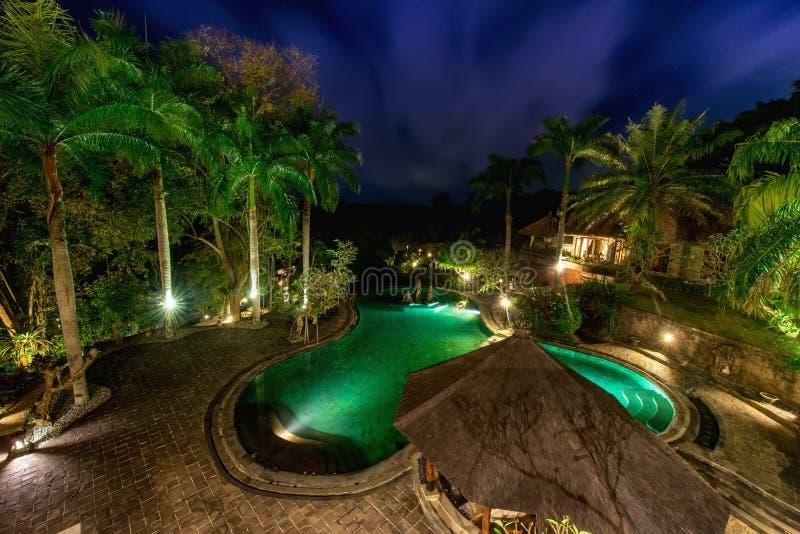 Vue de piscine d'infini à la villa luxueuse de jungle Beau jardin par nuit image libre de droits