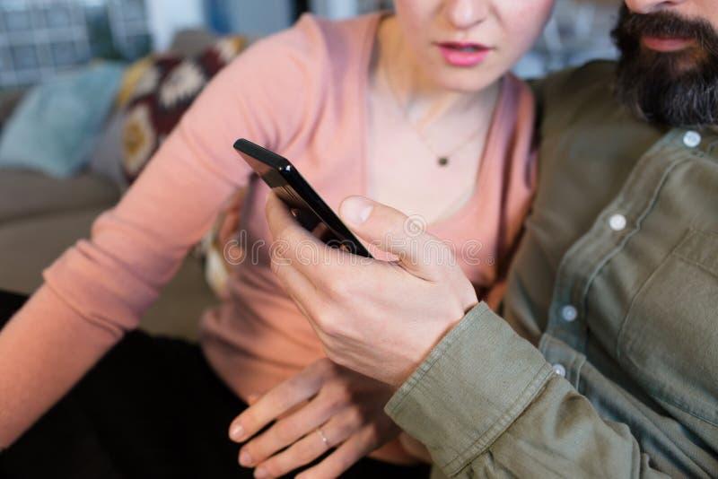 Vue de plan rapproché de beaux jeunes couples utilisant le smartphone à l'endroit de moder Relations romantiques entre les person photo stock