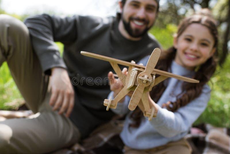 vue de plan rapproché d'avion en bois de jouet dans des mains de fille photos stock