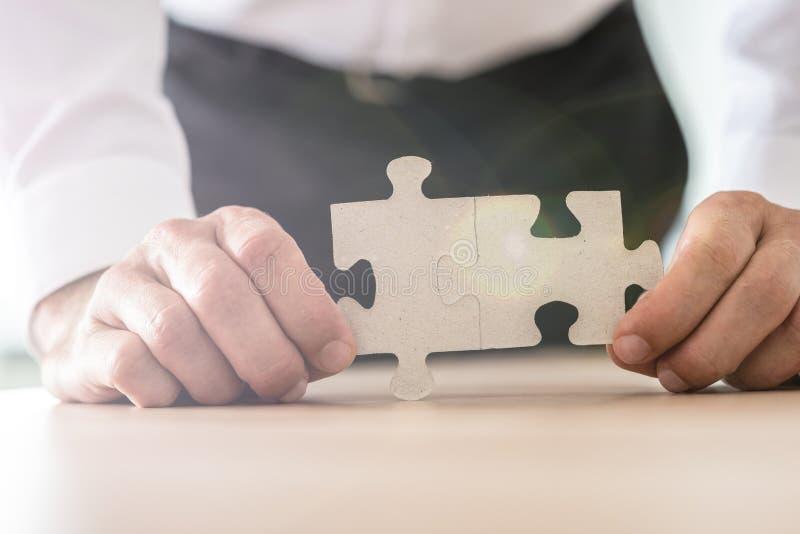 Vue de plan rapproché d'homme d'affaires tenant deux morceaux jointifs de puzzle photos stock