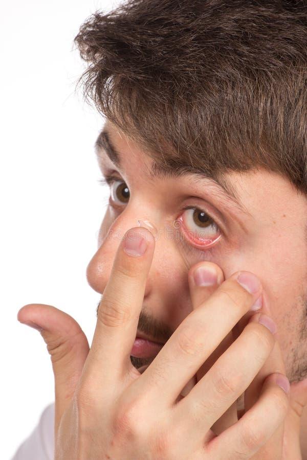 Vue de plan rapproché de l'oeil brun d'un homme tout en insérant un c correctif images stock