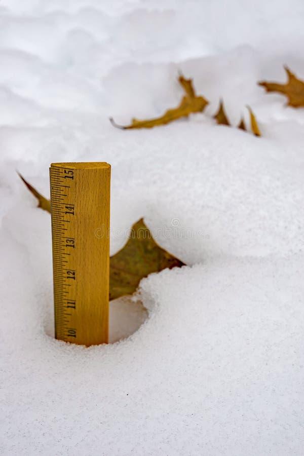 Vue de plan rapproché des chutes de neige de mesure d'hiver avec un critère photos stock