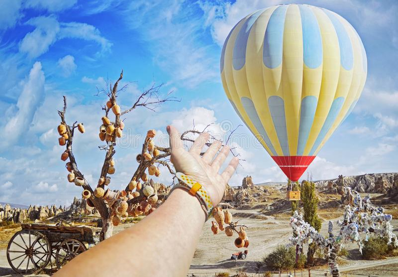 Vue de plan rapproché de main sur le vol chaud coloré de ballon à air au-dessus de la vallée image libre de droits