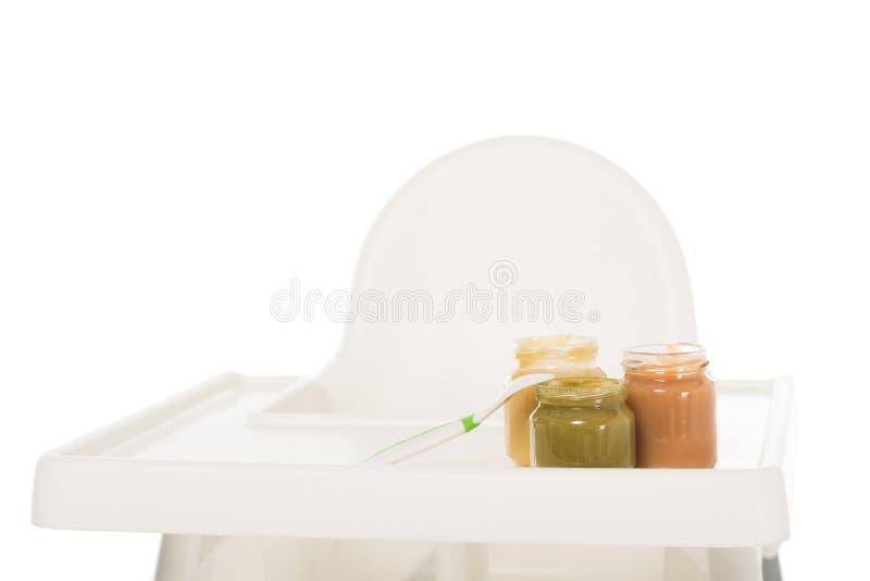 vue de plan rapproché de trois pots avec la purée et la cuillère d'enfant sur le highchair image stock
