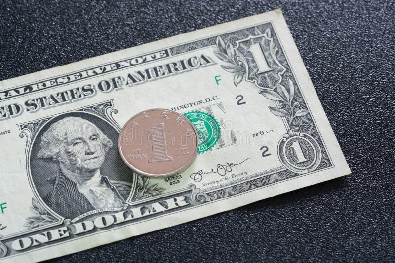 Vue de plan rapproch? de 1 yuan chinois sur un billet de banque des Etats-Unis du 1 dollar sur le fond fonc? photos stock