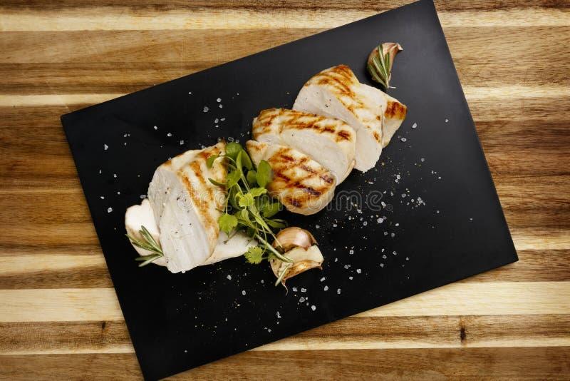 Vue de plan de sein succulent chevronné de poulet rôti, avec la garniture d'ail et de romarin image libre de droits