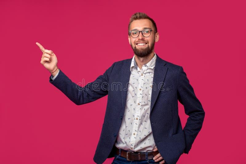 Vue de portrait d'un homme d'affaires heureux attirant avec des verres sur un fond rose images stock