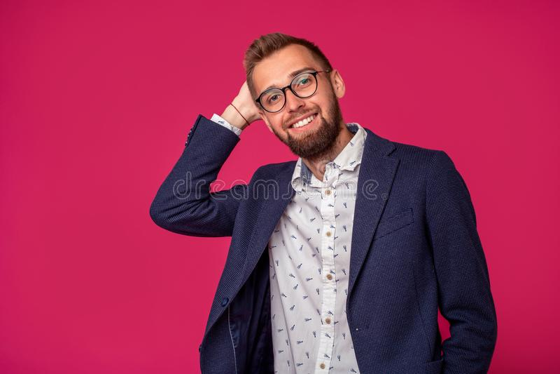 Vue de portrait d'un homme d'affaires heureux attirant avec des verres sur un fond rose photographie stock libre de droits