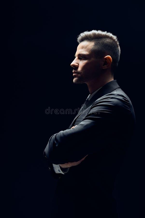 Vue de profil d'homme sûr dans le costume noir avec des bras croisés sur le fond foncé photos libres de droits