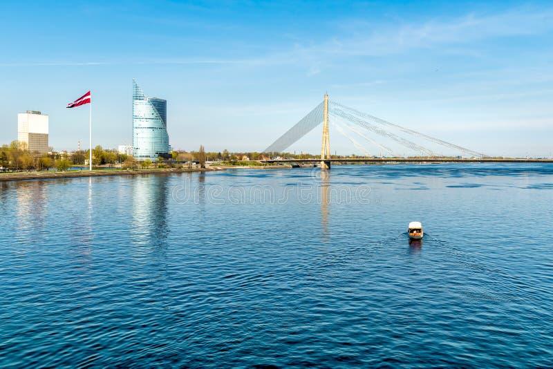 Vue de rivière de dvina occidentale avec le pont câble-resté, le drapeau letton et le bateau qui traverse la rivière, Riga photographie stock libre de droits