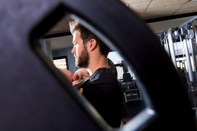 Vue de séance d'entraînement d'haltérophilie d'homme de Barbell par le trou images libres de droits