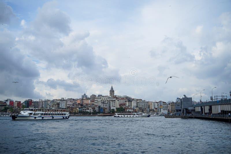 Vue de soirée du secteur de tour de Galata, pont avec les personnes pêchant et l'eau de mer du Bosphore avec des bateaux, des mou images stock