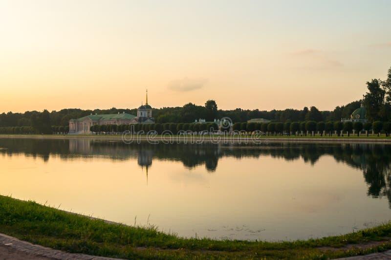 Vue de soirée par l'étang sur le palais et l'église avec la tour de cloche dans le musée-domaine Kuskovo, Moscou photo libre de droits