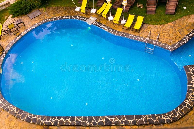 Vue de swimingpool avec les chaises jaunes à l'arrière-plan photographie stock libre de droits