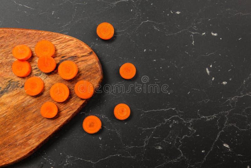 Vue de table, carotte coupée en tranches aux petits cercles sur un hachoir, certains sur le marbre noir après photo libre de droits