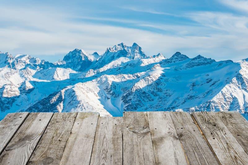 Vue de table en bois vide aux montagnes d'hiver photos stock