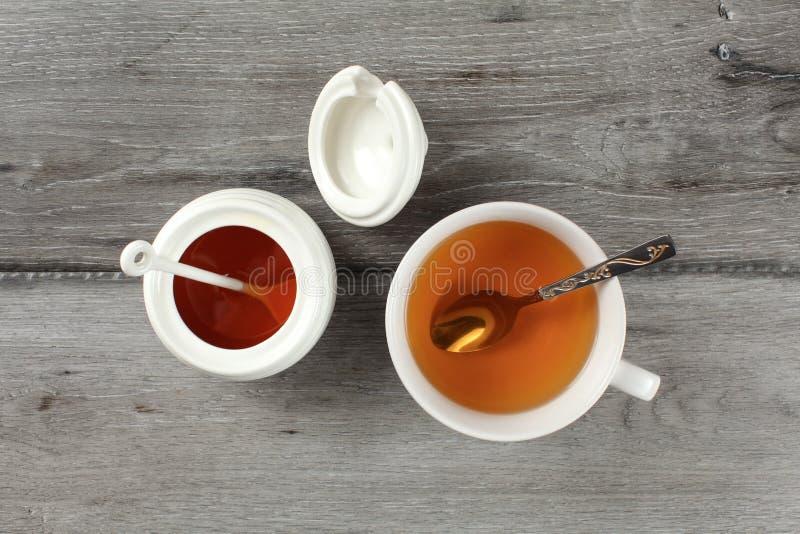 Vue de table sur la tasse blanche de porcelaine avec le spo chaud de thé et d'argent photo libre de droits