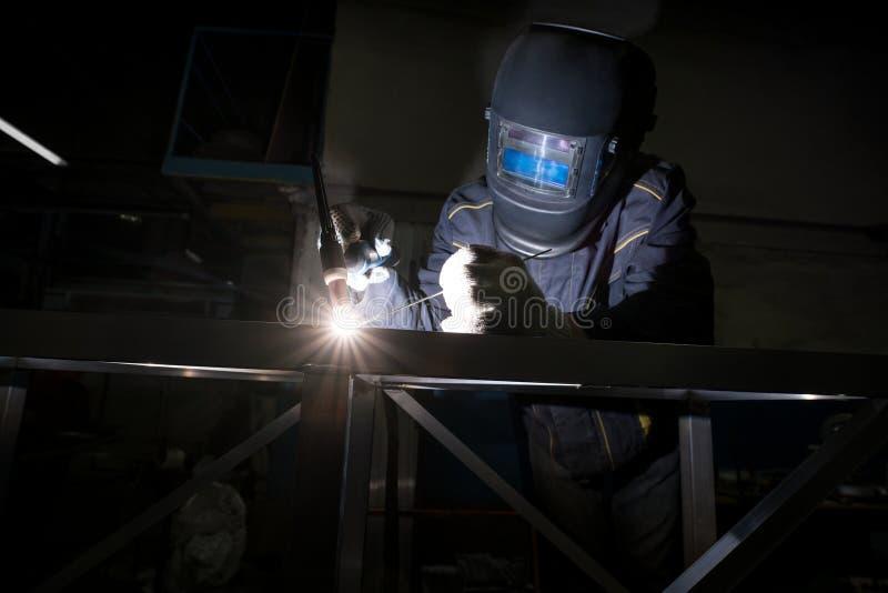 Vue de travailleur dans le masque de protection faisant la soudure d'argon photos stock