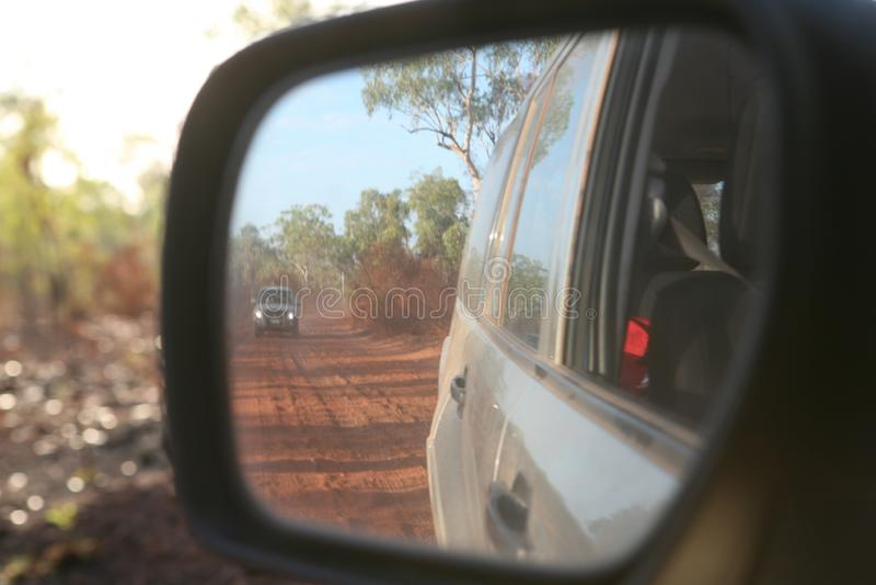 Vue de véhicule d'entraînement à quatre roues derrière dans le miroir arrière le long d'un rouge, route ondulée et poussiéreuse e photographie stock