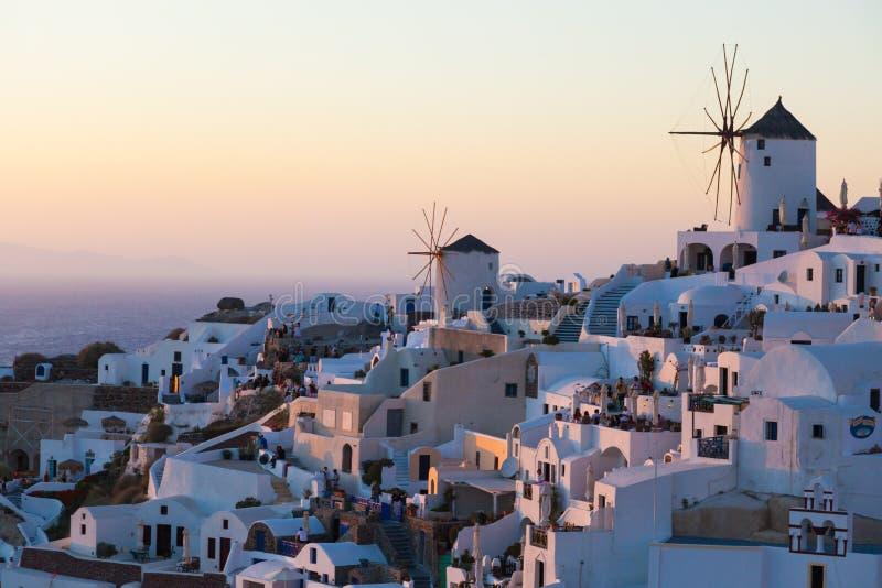 Vue de village d'Oia avec des moulins à vent au coucher du soleil, Santorin, Grèce photographie stock libre de droits