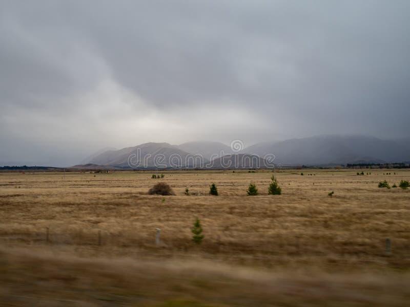 Vue des Alpes du sud, Nouvelle-Zélande, avec les nuages de pluie de apparence vague dans la distance photographie stock