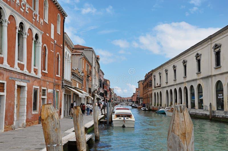 Vue des bâtiments, devant le canal, avec des personnes et des bateaux dans Murano photographie stock