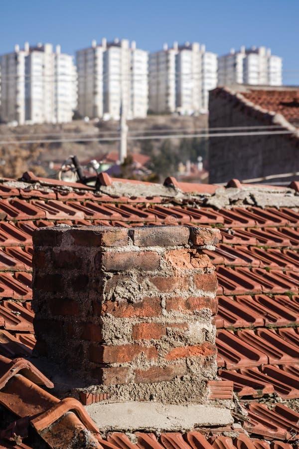 Vue des bâtiments urbains de transformation au-dessus d'un vieux dessus de toit de Chambre photo stock