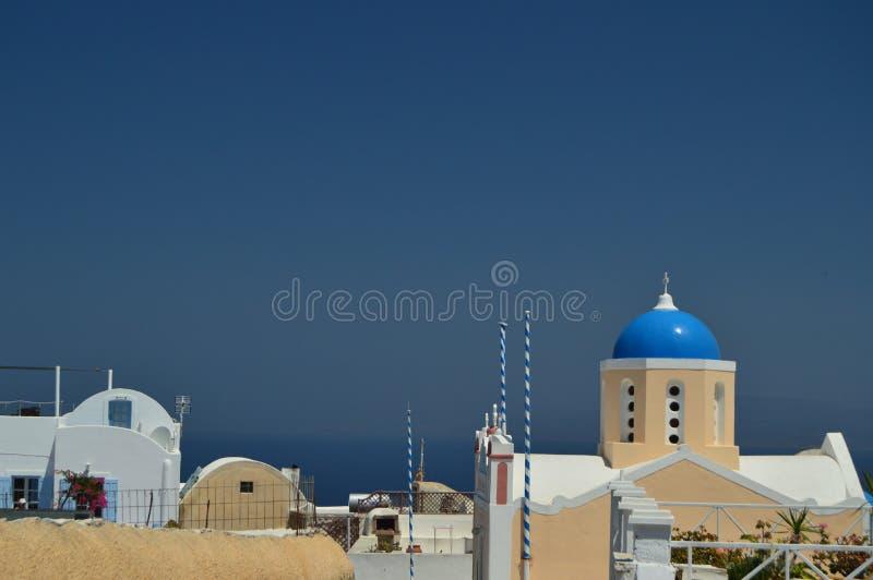 Vue des Chambres avec le dessus de toit sauté bleu avec la vue de la mer Égée bleuâtre en île de Santorini de ville d'Oia Archite image libre de droits