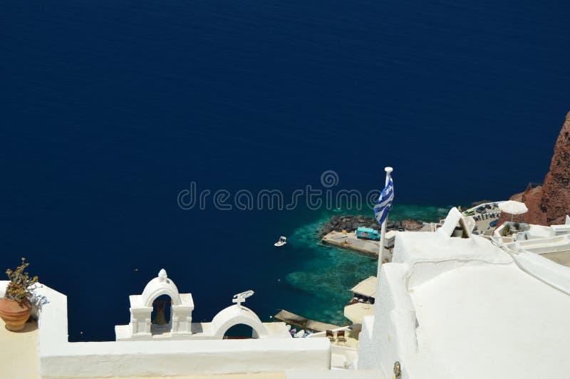 Vue des Chambres avec le dessus de toit sauté bleu avec la vue de la mer Égée bleuâtre en île de Santorini de ville d'Oia Archite photo libre de droits
