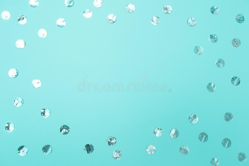 Vue des confettis argentés brillants sur le fond en pastel de papier de turquoise Concept des vacances, anniversaire, bloguant, b photo stock