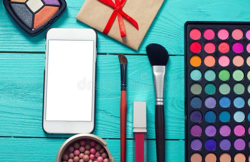 Vue des cosmétiques et de l'écran mobile vide sur le fond en bois bleu L'espace de vue supérieure et de copie Voir les mes autres photos libres de droits