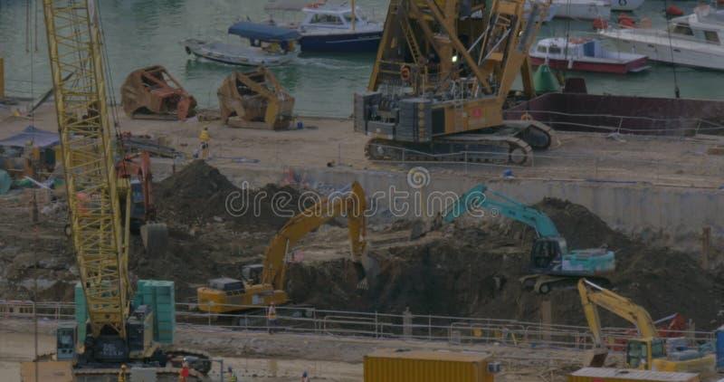 Vue des excavatrices creusant un trou près du dock Hong Kong, Chine clips vidéos