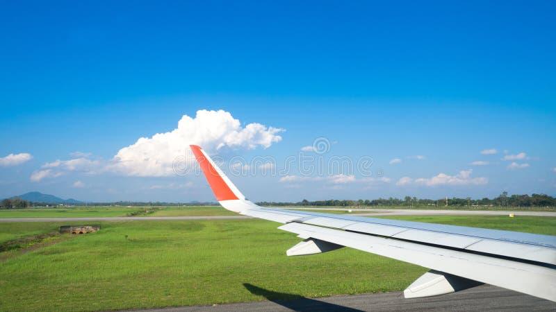 Vue des fenêtres d'avion de passager après le débarquement, de beau groupe de nuage, de ciel bleu et de paysage Avions d'aile dan photo stock